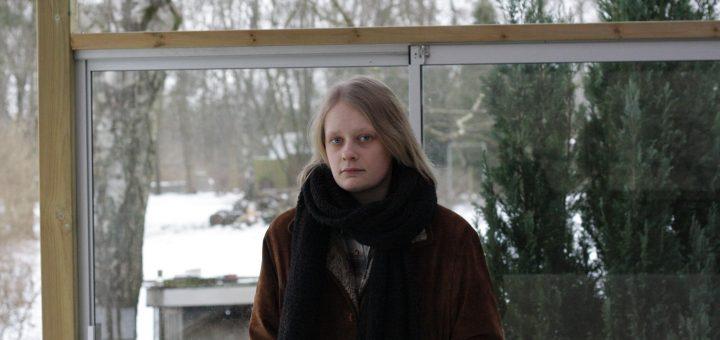 Ebba Ozolins, framför ett fönster med snö utanför och ytterkläder på.